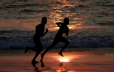 Youths play rugby on a beach in Colombo