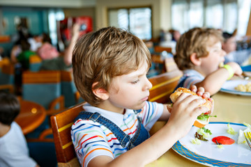 Cute healthy preschool kid boy eats hamburger sitting in school or nursery cafe. Happy child eating healthy organic and vegan food in restaurant. Childhood, health concept.