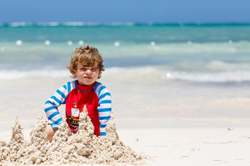 Adorable little blond kid boy having fun on tropical beach of carribean island. Excited child playing and building sand castle in sun protected swimsuit in ocean on vacations
