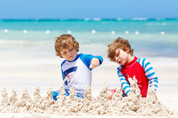 Two little kids boys having fun with building a sand castle on tropical beach of carribean island. children playing together on their vacations Twins, Happy brothers laughing and smiling.