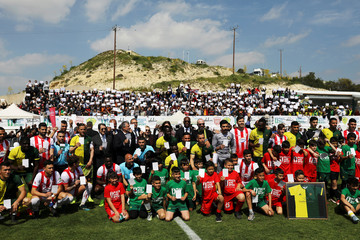 Cyprus President Nicos Anastasiades, Joel Bouzou and Didier Drogba, players and villagers hold white cards as they pose for a family photo before a friendly game in Pyla