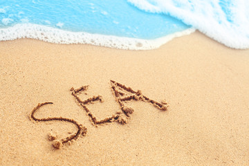 Sea beach. Sand and blue surf texture background with hand drawing text. Vacation and holiday concept