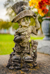 A aged alabaster boy grave statue on a grave. The boy is holding his hat, and there is also a dog t as well by his leg. The alabaster has discolored from the elements.