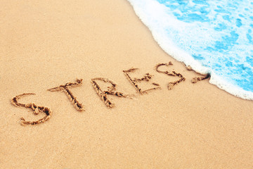 Stress free travel. The wave on sea beach washes away sign stress on sand