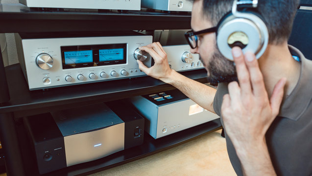 Man turning up the volume on home Hi-Fi stereo