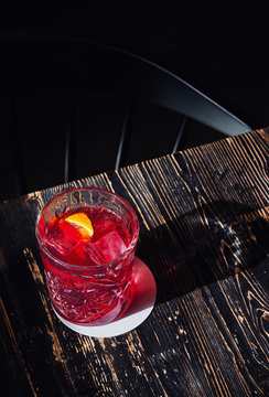 Red cocktail in glass garnished with a wedge of orange