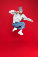 Full length photo of beautiful man smiling and jumping isolated over red background