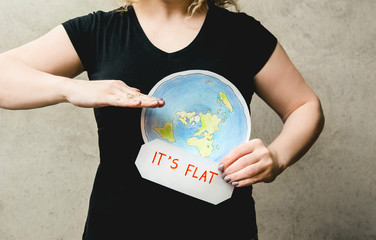 Flat Earther concept. Person who believes that Earth is flat disc. Anonymous woman holding flat Earth model in front of body with text: It`s flat. Isolated on gray background, studio shot.
