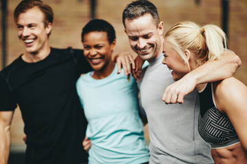 Friends laughing after a workout together in a gym