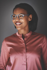 Smiling young African businesswoman standing against a gray back