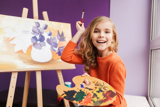 Cute little girl drawing a picture on canvas