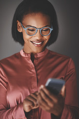 Smiling African businesswoman using her cellphone against a gray