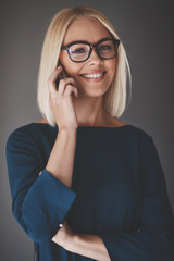 Smiling businesswoman talking on her cellphone against a gray ba
