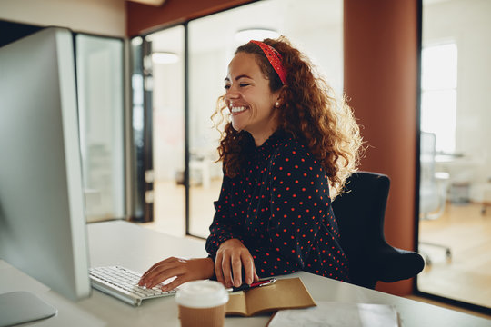 Laughing young businesswoman working on her office computer