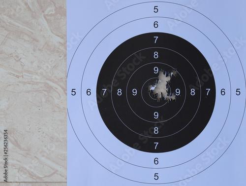 Closeup of gun shot mark at center of paper target  Symbol