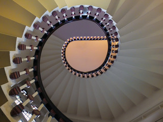 a looking upwards view of an elegant spiral staircase with wooden bannisters in elegant shades of white