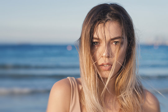 Portrait of a beautiful female model with blond wet hair standing near ocean or sea shore. Sensual look