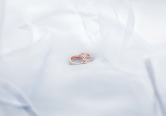 Wedding rings on white transparent fabric. Horizontal photo