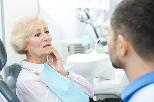 Senior woman suffering from toothache visiting dentist