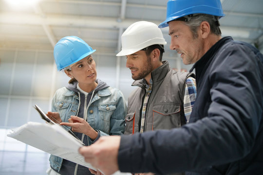 Team of construction workers talking in empty warehouse