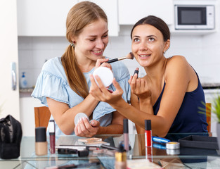 Two smiling young women friends doing make-up  at table with cosmetics