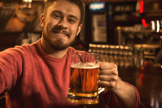Cheerful handsome young man taking a selfie while drinking beer at the bar