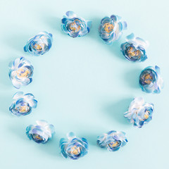 Flowers composition creative. Wreath made of light blue flowers on pastel blue background. Flat lay, top view, copy space