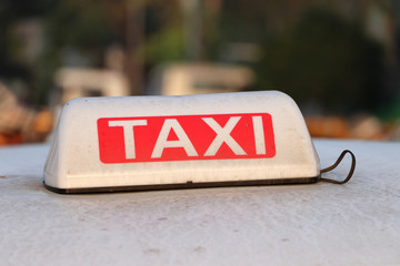 Taxi light sign or cab sign in white and red color with white text on the car roof at the street blurred background.