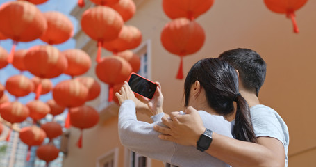 Couple use of mobile phone for take photo with red lantern