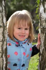 Portrait Kleines glückliches Mädchen zwischen Baumstämmen
