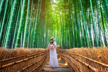 Fototapete - Woman walking at Bamboo Forest in Kyoto, Japan.