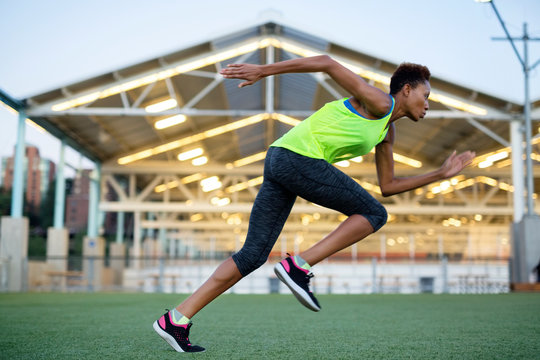 Athlete running on grassy field