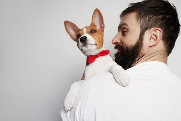 Handsome happy man snuggling and hugging his basenji puppy dog, close friendship against a white background