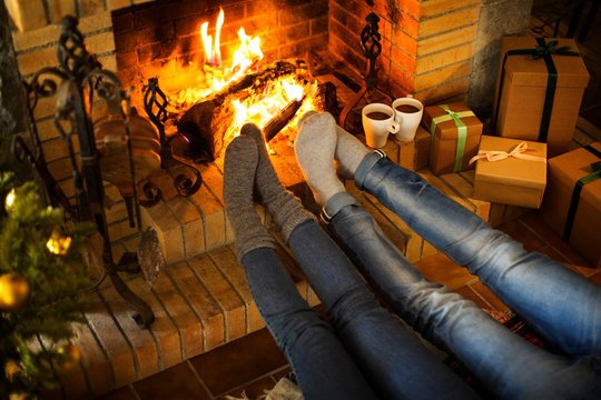 Low section of couple resting by fireplace and Christmas presents at home