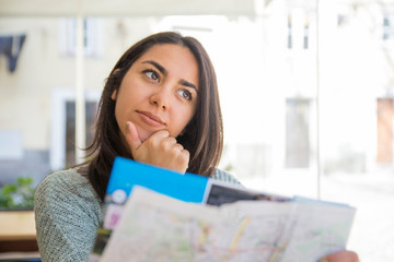 Dreamy pretty young woman using paper map in cafe