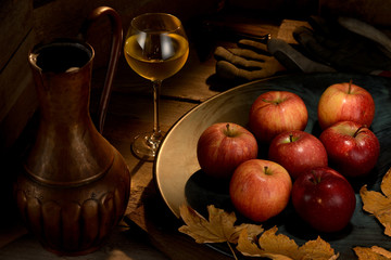 A still life with apples and wine, work gloves and penknife. The hard work of the autumn harvest demands the reward.