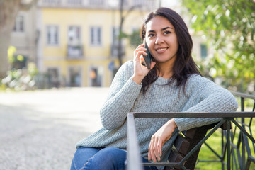 Relaxed woman talking on phone and sitting on bench outdoors