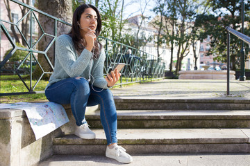 Serious young woman listening to music on city stairs parapet