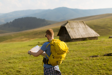 Young redhair man on mountain hiking holding a map