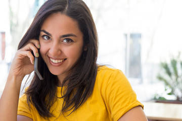 Smiling beautiful young woman talking on smartphone