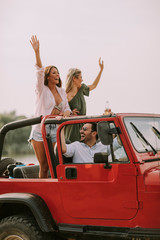 Group of happy young friends having fun in convertible car during summer vacation