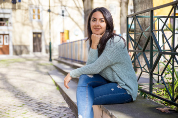 Smiling pretty young woman sitting on stone bench outdoors