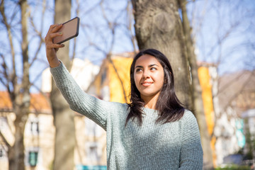 Smiling pretty young woman taking selfie photo outdoors