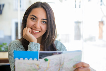 Smiling pretty young woman using paper map in cafe