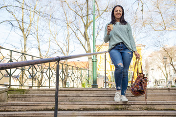 Smiling pretty young woman walking down city stairs