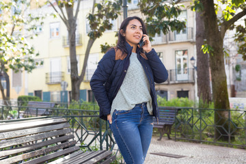 Smiling woman calling on mobile phone outdoors