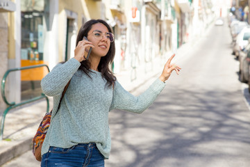 Smiling woman talking on phone and hailing for taxi