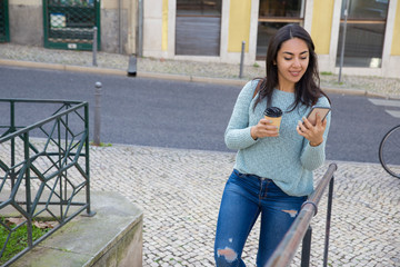 Smiling woman using smartphone and walking up city stairs