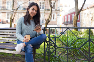 Smiling woman using smartphone on bench outdoors