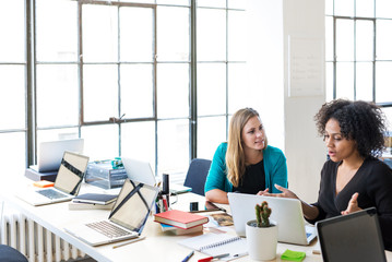 High angle view of businesswomen talking while working at office